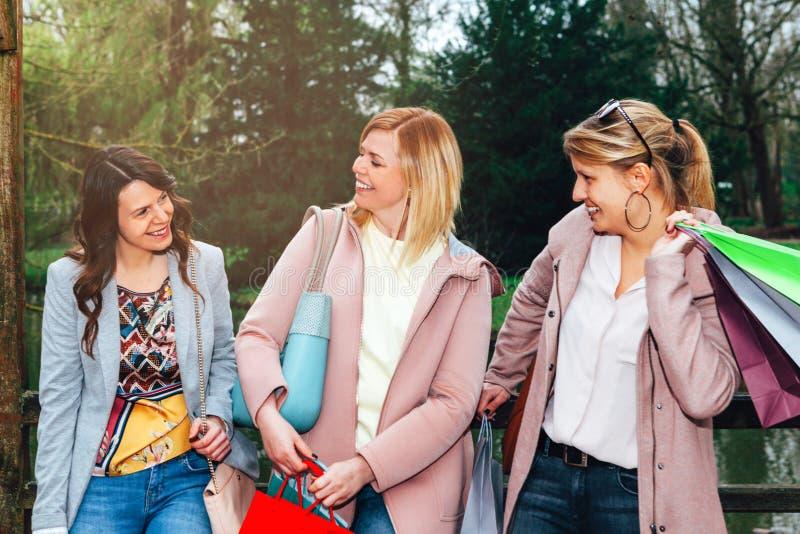 女性朋友小组获得乐趣一起在城市公园在购物以后 免版税图库摄影