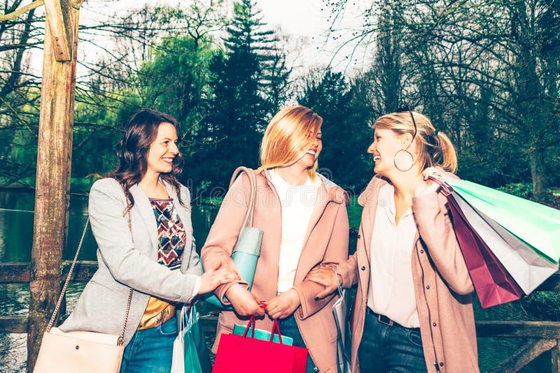 女性朋友小组获得乐趣一起在城市公园在购物以后 免版税库存照片
