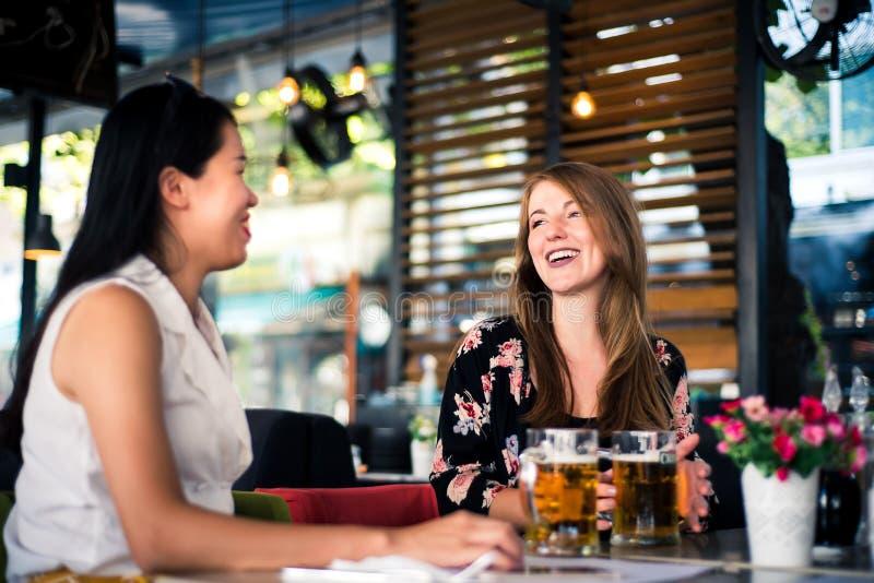 女性朋友有谈话在酒吧 免版税库存图片