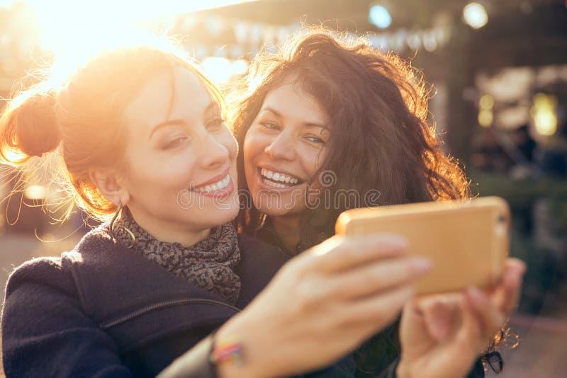 女性朋友采取selfie的两名妇女在周末逃走期间户外 免版税图库摄影