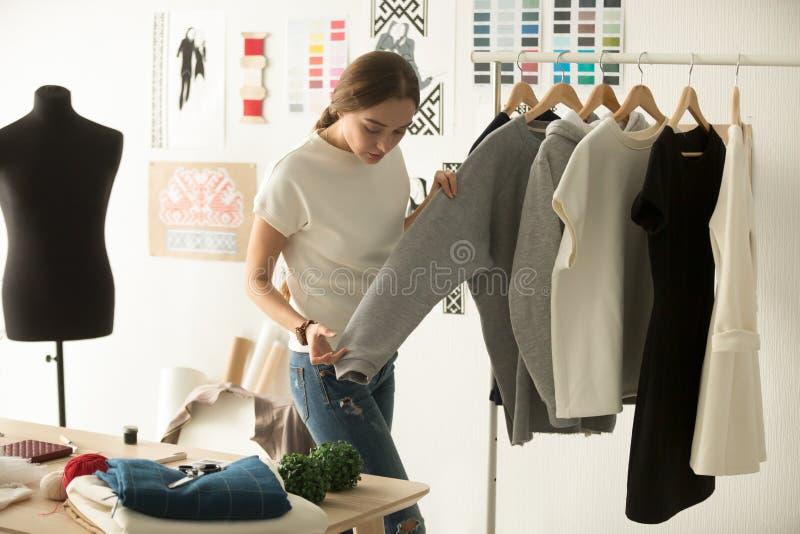 女性服装设计师与新的女服一起使用在车间 免版税库存图片