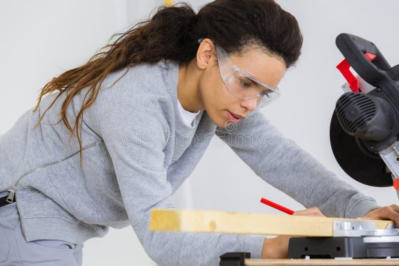 女性木匠测量的和指示的木头 库存图片