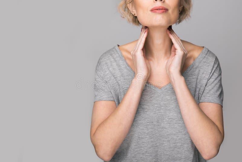 女性检查的甲状腺由她自己 关闭接触与红色斑点的白色T恤的妇女脖子 甲状腺 免版税库存照片