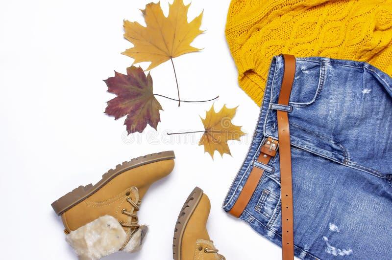 女性橙色被编织的毛线衣、蓝色牛仔裤、起动和秋叶在白色背景顶视图平的位置 时尚Clothes Set夫人的 库存图片