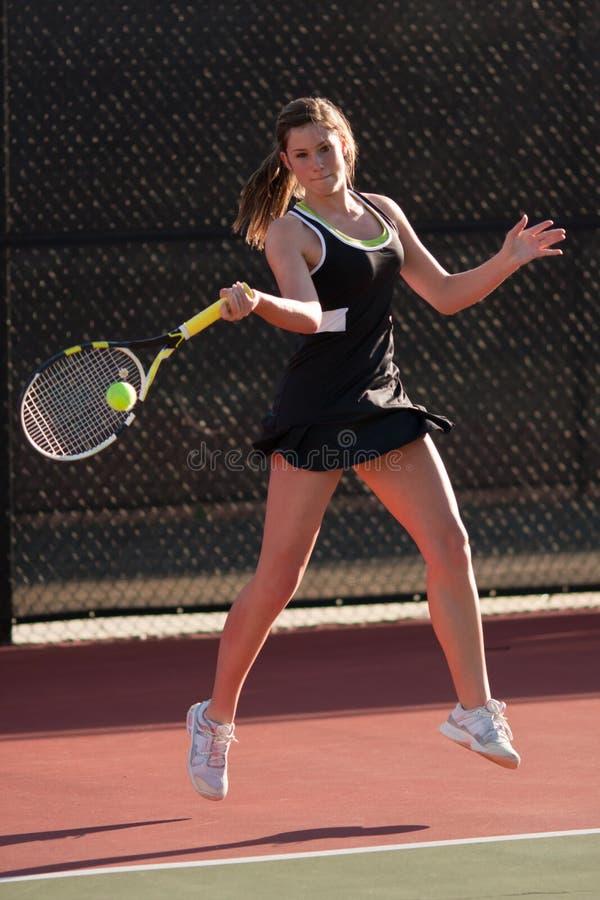 女性正手击球符合球员击响网球 免版税库存照片