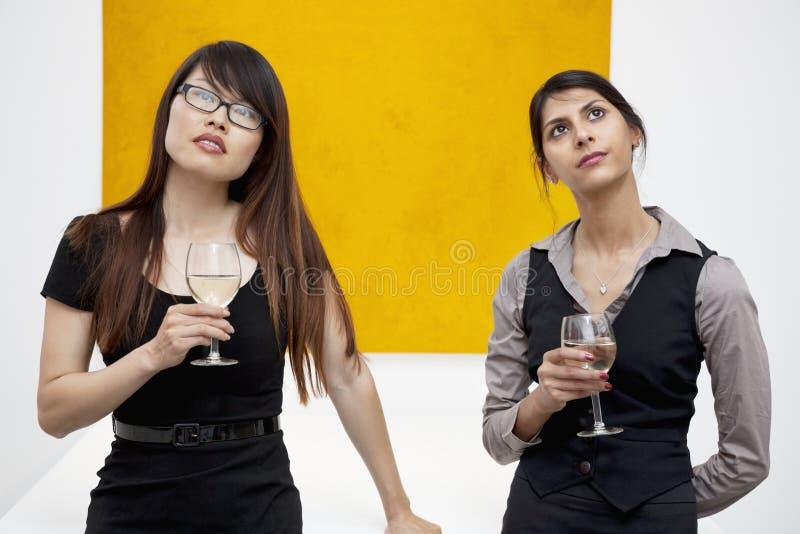 年轻女性正面图有查寻在美术画廊的酒杯的 图库摄影