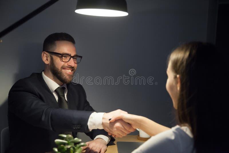 女性求职者的愉快的男性震动的手在采访中的 免版税库存照片