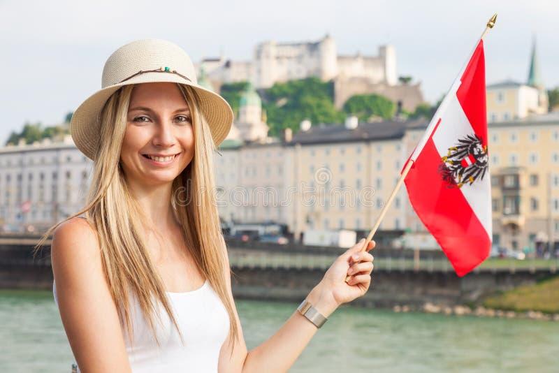 女性游人在度假在萨尔茨堡拿着奥地利旗子的奥地利 免版税库存图片