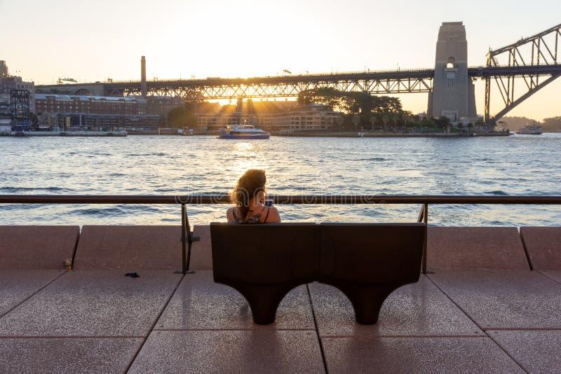 女性游人坐的和观看的日落 免版税库存图片