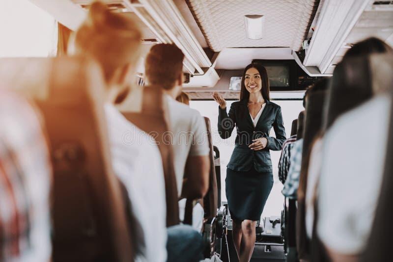 女性游览服务雇员在游览车的工作 免版税库存图片