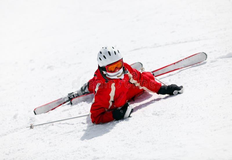 女性滑雪者在跌倒下来山坡以后 库存照片