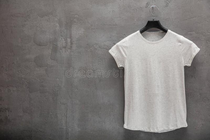 女性灰色混合物棉花T恤杉的前方在一个挂衣架和一个混凝土墙的在背景中 免版税库存照片