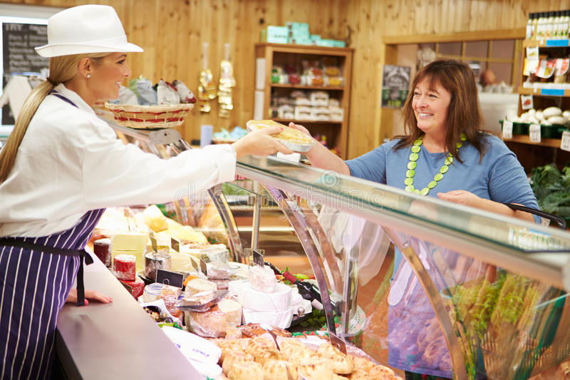 女性熟食的销售辅助服务顾客 免版税库存图片