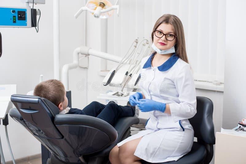 女性牙医审查和与男孩患者一起使用 牙医` s椅子的孩子男孩 库存照片