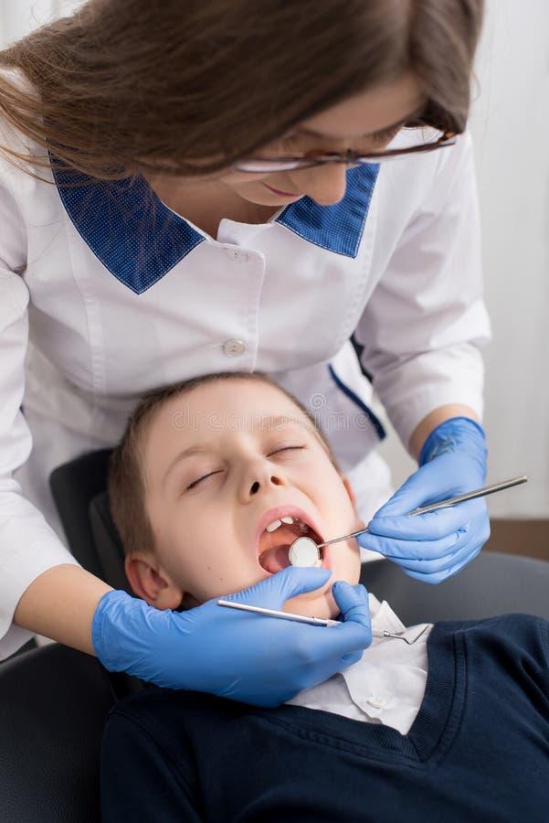 女性牙医审查耐心孩子的牙 免版税库存照片
