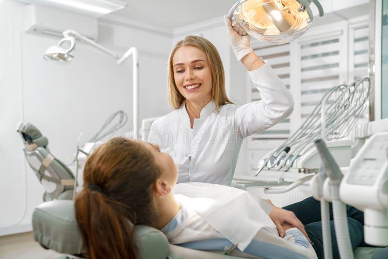女性牙医谈话与说谎在牙齿椅子的患者 库存图片