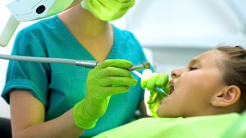 女性牙医钻井十几岁的女孩牙,龋撤除,健康口腔 库存图片