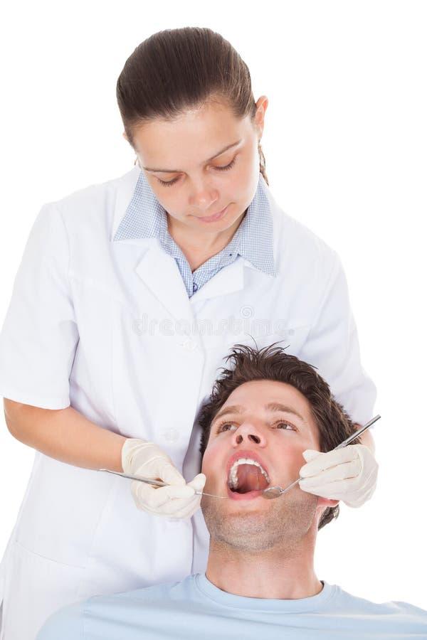 女性牙医审查的患者 免版税库存图片