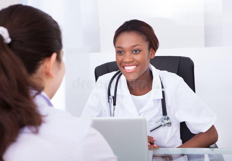 女性牙医谈话与患者在诊所的书桌 免版税库存照片