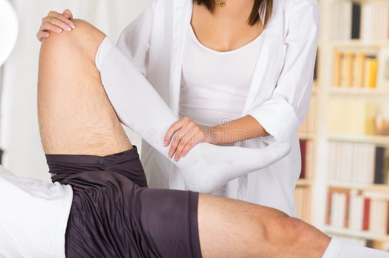 女性理疗的治疗师递工作在男性患者低腿和脚腕,弯曲的膝盖,模糊的诊所背景 库存照片