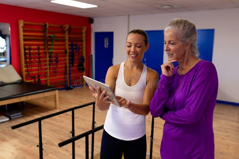 女性生理治疗师谈论与残疾资深妇女在一个现代体育中心 库存图片