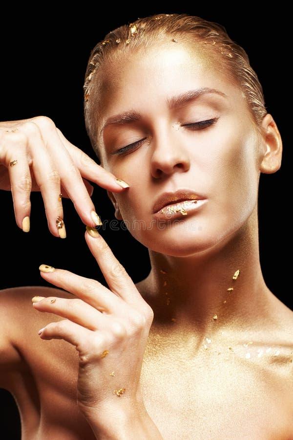 女性用手临近面孔 黑背景的金黄女孩 免版税图库摄影