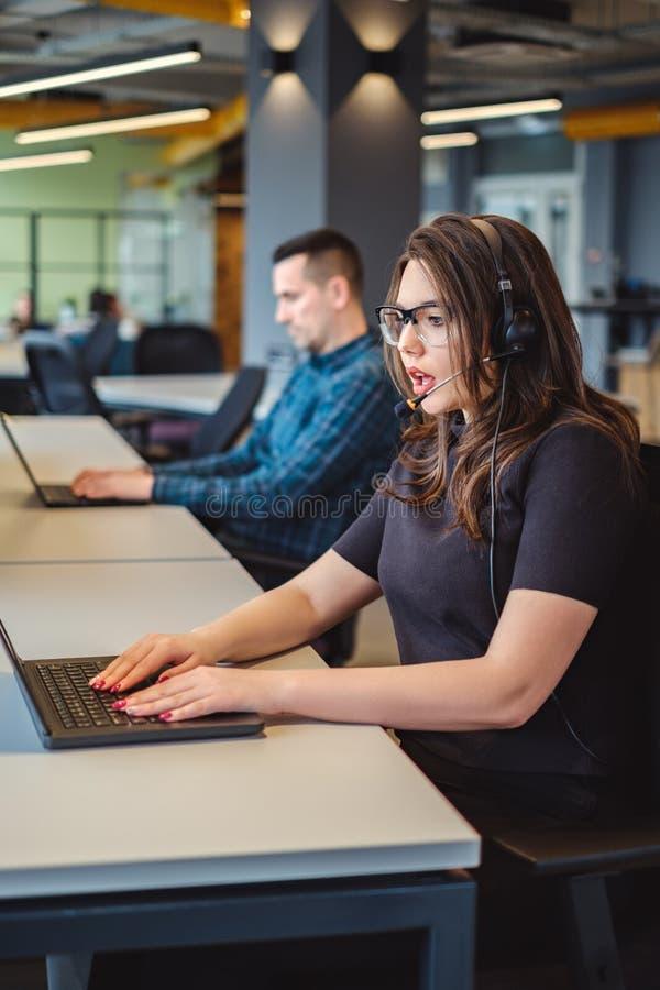女性电话中心操作员严重谈话在耳机 免版税图库摄影