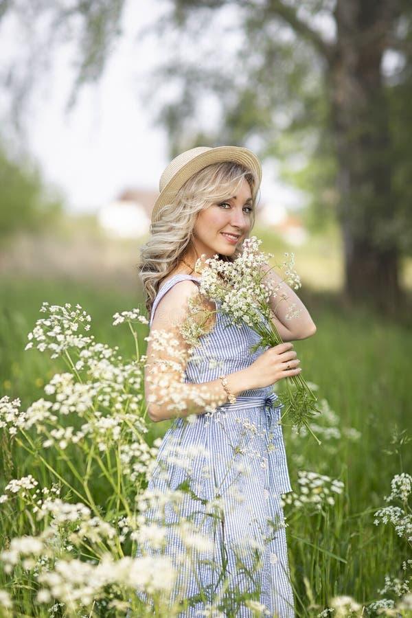 女性画象户外 一个草帽的一名妇女在与野花花束的一块花田  免版税库存图片