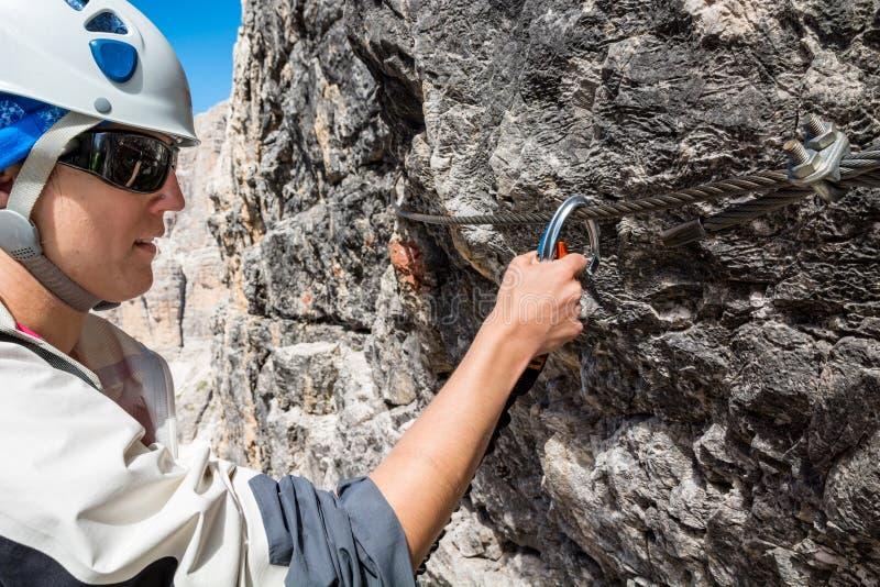女性登山人通过ferrata路线 免版税库存照片