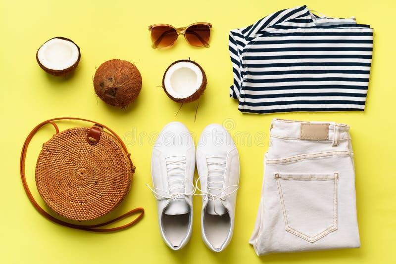 女性白色运动鞋、牛仔裤、镶边T恤杉、藤条袋子、椰子和太阳镜在黄色背景与拷贝空间 免版税库存照片
