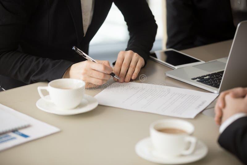 去女性的手签署文件,举起署名,关闭 免版税图库摄影
