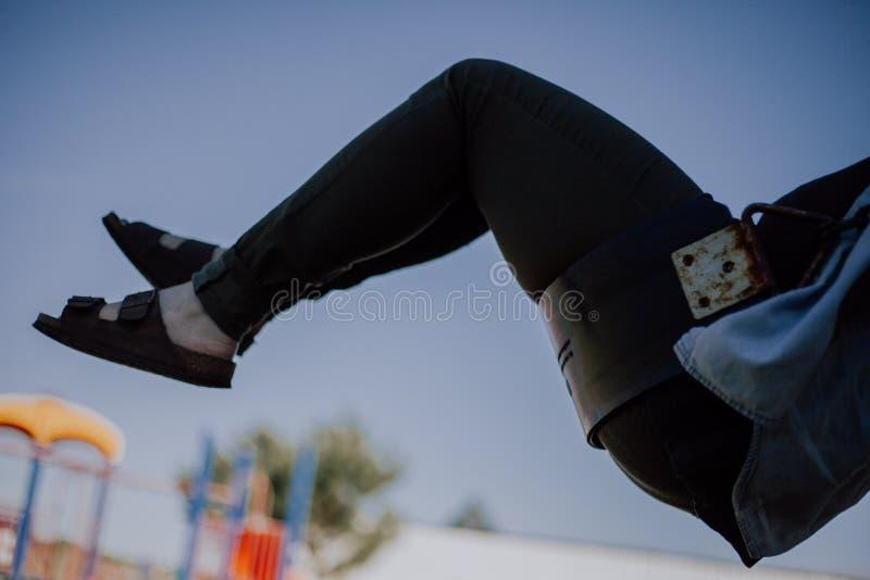 女性的脚在天空中,当坐摇摆有被弄脏的背景时 库存图片