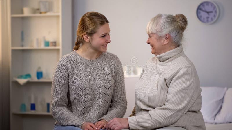 女性看的志愿者和愉快的退休的夫人坐的医院病床 免版税库存照片