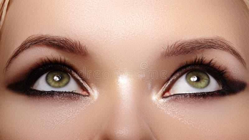 女性眼睛美丽的宏观射击与时尚黑发烟性构成的 化妆用品和构成 黑暗的眼影膏 ?? 库存照片