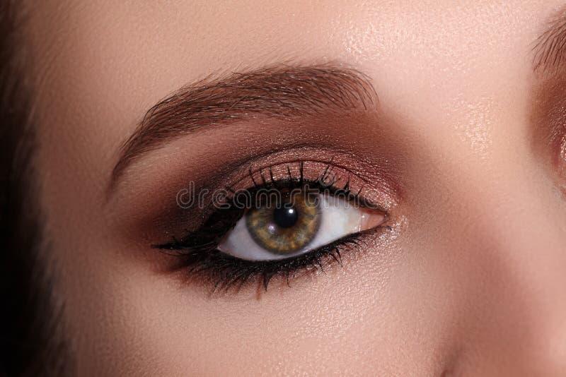 女性眼睛美丽的宏观射击与经典眼线膏构成的 眼眉完善的形状  化妆用品和构成 库存照片