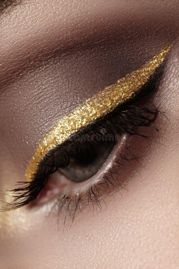 女性眼睛美丽的宏观射击与礼仪构成的 眼眉完善的形状,眼线膏和俏丽的金子在眼皮排行 免版税库存图片