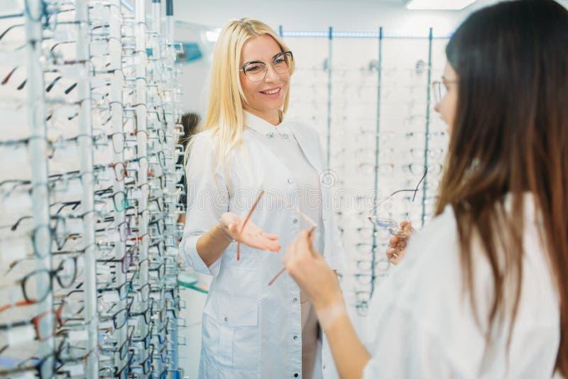 女性眼镜师和顾客shooses玻璃 免版税库存照片