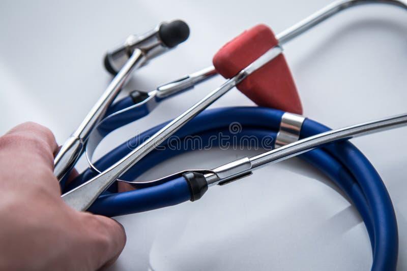 女性神经学家与听诊器,大型装配架和Tylor反射锤子一起使用 免版税库存照片
