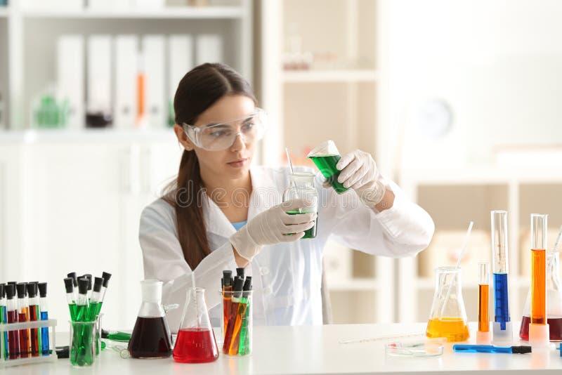 女性科学家落下的颜色样品到测试烧瓶里在实验室 免版税库存图片
