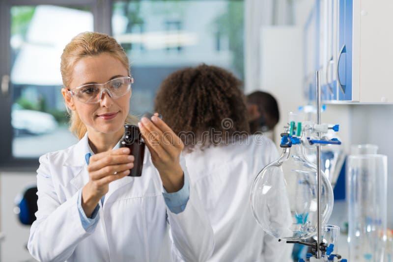 女性科学研究员在做研究,妇女的实验室与在小组的化学制品一起使用科学家 免版税图库摄影