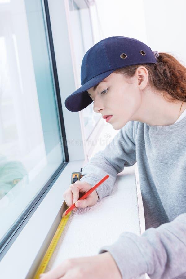 女性窗口安装员测量的窗口 免版税库存图片