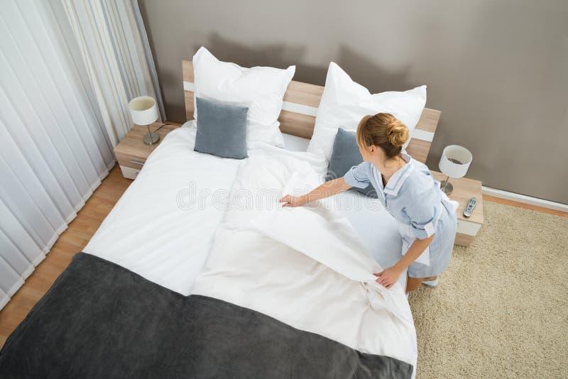 女性管家改变的卧具 库存图片