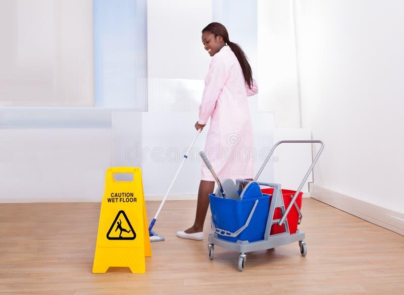 女性管家清洁地板在旅馆里 免版税库存照片