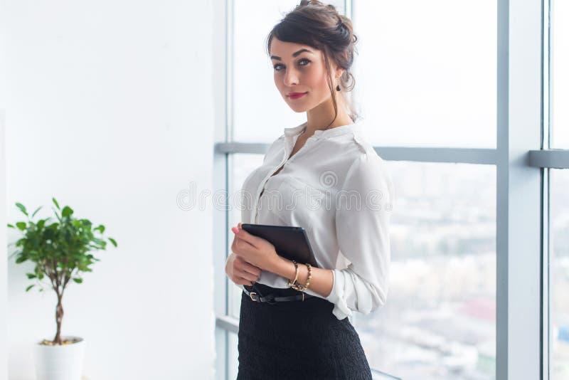 女性经理佩带的办公室衣服,身分,藏品片剂在她的手上,看照相机 免版税库存图片