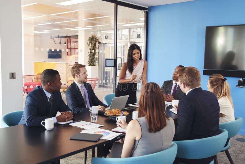 女性经理在会议室站立对同事演讲 免版税库存图片