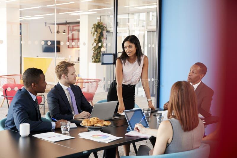 女性经理在会议站立对同事演讲 免版税库存图片