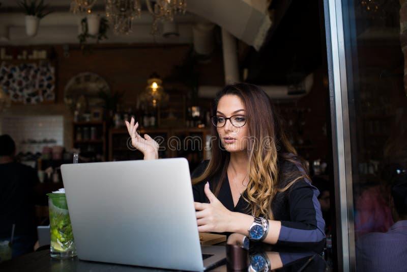 女性经理有网上电话通过笔记本设备 Webinar通过netbook 免版税库存图片