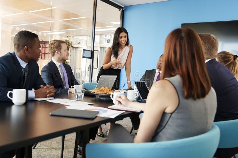 女性经理站立对队演讲在业务会议上 库存照片
