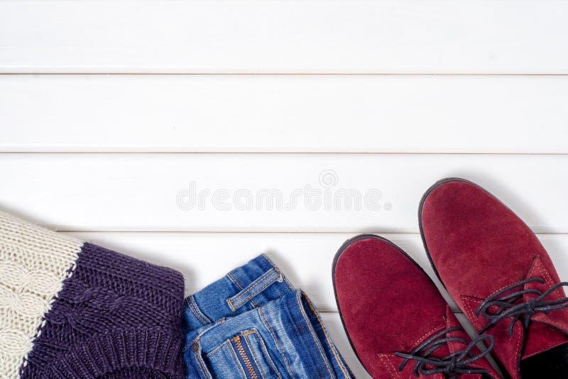 女性绒面革穿上鞋子毛线衣牛仔裤 免版税图库摄影