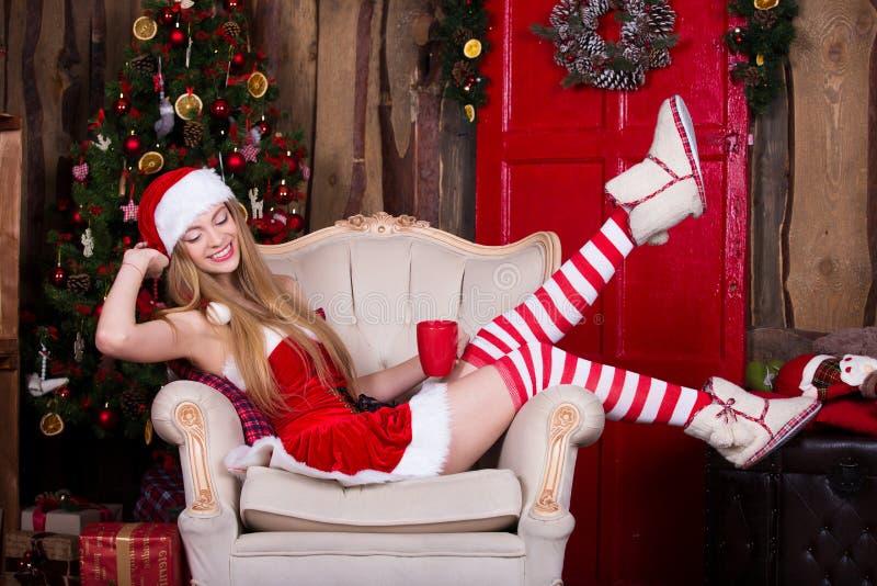 女性美丽,性感的圣诞老人获得乐趣和微笑在圣诞树附近,坐在葡萄酒椅子 新年度 免版税图库摄影